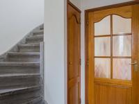Indeling hoofdwoning. Begane grond: <BR><BR>Entree met een warme leistenen vloer, trapopgang en gemoderniseerd toilet.  <BR><BR>Vanuit de hal loopt u de woonkeuken in waar diezelfde vloer doorloopt, de wanden zijn voorzien van een lambrisering, het plafond is gestuukt. De kelderkast geeft extra bergruimte. De keuken is in 2000 vernieuwd en voorzien van een hardstenen blad, koelkast, keramische kookplaat, RVS afzuigkap, vaatwasser en magnetron. <BR><BR>In de L-vormige woonkamer ligt ook een leistenen vloer met vloerverwarming en er is hier een fraai gestuukt plafond met sierlijst en inbouwspots. De openslaande tuindeuren bieden toegang tot het overdekt terras. <BR><BR>Vanuit de keuken biedt een portaal toegang tot de tuin en doorgang naar de 2e woning.
