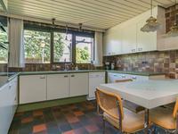 De dichte keuken is ruim van opzet, heeft diezelfde tegelvloer en een keukeninrichting voorzien van een inductie kookplaat, afzuigkap, 2 RVS spoelbaken, vaatwasser, oven en koelkast. Het grote raam boven het aanrecht zorgt voor veel licht. <BR>Er is een inpandige doorgang tot de aangebouwde garage.<BR>Vanuit de keuken is ook de provisieruimte met legplanken bereikbaar.