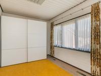 Slaapkamer 2 ligt aan de achterzijde en heeft een vaste wastafel.