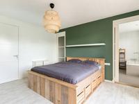 Eerste verdieping:<BR>Ruimtelijke overloop met een laminaatvloer en stucwerk wanden en plafond. <BR>De mooie ouderslaapkamer heeft een badkamer en-suite. Deze is betegeld en voorzien van een wastafel, ligbad en inloopdouche. Op de slaapkamer is ook toegang tot een grote inloopkast. Aan de achterzijde zijn twee slaapkamers met laminaatvloer en stucwerk wanden en plafond. <BR>Er is nog een geheel betegelde wasruimte, welke is voorzien van een wastafel en inloopdouche. Ook is er toegang tot een apart betegeld toilet.