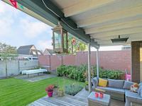 Buiten de woning:<BR>Achter aan de woning is een fraaie veranda geplaatst welke de woonkamer door laat lopen in de tuin. Hier ligt een houten vlonder en er is ene buitenhaard aanwezig. Verder is de tuin voorzien van gras, diverse beplantingen en een vrije achterom.