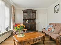 L-vormige woonkamer voorzien van een mooie houten vloer (voorzien van vloerisolatie), lichte stucwerk wanden en plafond en een mooie inbouw gashaard.