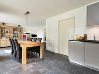 De keuken is open en de eettafel verbindt het geheel met de woonkamer. De tegelvloer is voorzien van het comfort van vloerverwarming en de schuifpui naar het terras geeft extra lichtinval.