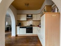Vanuit de woonkamer komt u in de open keuken met een veel licht doorlatende serre/tuinkamer waar het plafond open is tot in de nok. Deze ruimte is ideaal als speel-/ lees- of eethoek.  De houten vloer loopt hier en in de keuken door.  <BR>De keuken heeft een MDF hoekinrichting welke is voorzien van een ingebouwde koelkast, afzuiging, gasfornuis, oven en aansluiting voor de vaatwasser.