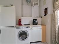 Praktische bijkeuken met tegelvloer, aansluiting voor wasapparatuur en opstelling cv-installatie.