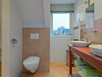 Geheel betegelde, nette badkamer voorzien van 2e toilet, wastafel, inloopdouche en dakkapel.