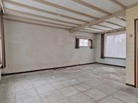 De L- vormige woonkamer is thans voorzien van een balken plafond en wanden zijn deels bekleed met houten afwerking.