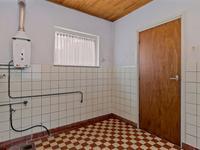 Vanuit de keuken komt u in de bijkeuken.  Deze is afgewerkt met een tegelvloer, voorzien van een een inbouwkast en u treft hier de geiser en de aansluitingen voor de wasmachine en droger. Tevens is hier het toilet.