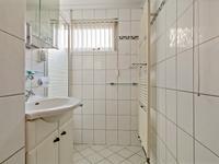De geheel betegelde badkamer is voorzien van een douche, een wastafelcombinatie, inbouwverlichting en mechanische ventilatie.