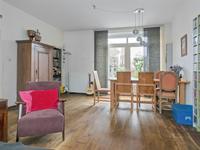 De knusse woonkamer heeft een warme houtenvloer, een schuurwerk plafond en aan de achterzijde brede openslaande tuindeuren.