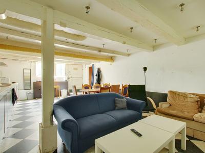 Entree, woonkamer en open keuken met inbouwapparatuur.