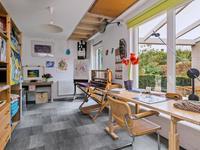 Aan de achterzijde is het atelier met een deur en ramen naar de tuin gevestigd. De hoogte in deze ruimte biedt een fijne omgeving om te schilderen, te werken of het realiseren van een speel- of slaapkamer.