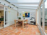 Grote serre (de tuinkamer) met tegelvloer, vloerverwarming en deuren met veel glas naar de achtertuin.