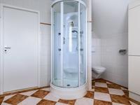Volledig betegelde badkamer voorzien van een ronde stoom-douchecabine met zijstralers en een thermostraatkraan, <BR>een mooi badmeubel met vaste wastafel, wandcloset en designradiator.