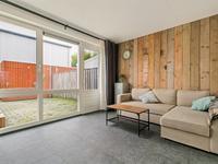 De woonkamer is afgewerkt met een mooie tegelvloer, een fraaie steigerhouten wand en een achterdeur.<BR>Bovendien is er een praktische trap-/provisiekast; prima te gebruiken voor extra bergruimte!