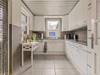 In de aanbouw is de hoekkeuken opgesteld welke is voorzien van een koelkast, keramische kookplaat, afzuigkap, vaatwasser en de aansluiting van de wasmachine en droger.