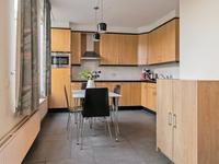 Tuingericht is de open keuken gesitueerd waar de tegelvloer met vloerverwarming doorloopt. <BR>Mooie MDF hoekkeuken met de nodige inbouwapparaten, namelijk koelkast, keramische kookplaat, afzuigkap, combi magnetron en vaatwasser. De provisiekast biedt de gevraagde bergruimte.
