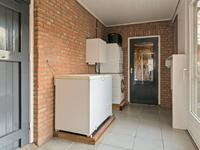 Vanuit de keuken kunt u naar de bijkeuken van waaruit u naar de oprit kunt maar ook kunt doorlopen naar de garage. In de bijkeuken zitten de aansluitingen voor de wasmachine en droger en een schuifdeur naar het terras.