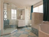 De badkamer is volledig betegeld en uitgevoerd met een wandcloset, wastafelmeubel met spiegel en kastjes, grote douche en ligbad.