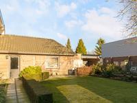 De achtertuin is netjes aangelegd met een zonneterras, gazon, groene borders en een kippenren.