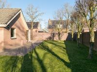 De tuin is netjes en verzorgd aangelegd met zowel een voor-, zij- als achtertuin. Er is een mooi terras, diverse paadjes, groene borders met begroeiing en voldoende speelruimte op het gazon. Aan de rechterzijde is een vrije achterom en links naast het kantoor is nog een berging aanwezig.