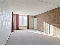 Doorzon woonkamer met vloerbedekking, deels behangen en deels metselwerk wanden en spuitwerk plafond.