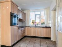 Aan de achterzijde is de open keuken gesitueerd. Deze is voorzien van een tegelvloer en een keukeninrichting met granieten aanrechtblad, koelkast, afzuigkap, keramische kookplaat, combi magnetron, vaatwasser en 1,5 spoelbak.