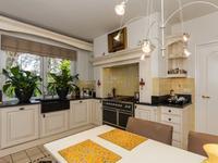 Keuken van 3.97 x 3.50 voorzien van stylvolle hoekopstelling met gasfornuis, afzuigschouw, oven, koelkast, vrieskast, vaatwasmachine, bijkeuken van 4.47 x 2.47 voorzien van wasmachine-aansluitingen.