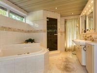 Luxe betegelde badkamer met groot ligbad in plateau, stoomcabine, dubbele wastafel in badmeubel, (badkamer en grote slaapkamer hebben toegang tot balkon).