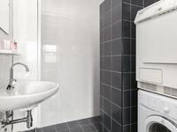 De badkamer is volledig betegeld en heeft naast de wastafel een inloopdouche en de aansluiting voor een wasmachine en droger.