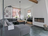 De L- vormige woonkamer heeft dezelfde natuurstenen vloer en is voorzien van een ingebouwde haard waaromheen het heerlijk vertoeven is in de tv hoek.