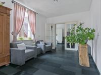 Via de deuren met veel glas is de doorkijk naar de woonkeuken aanwezig waar de vloer vanuit de kamer doorgelegd is.