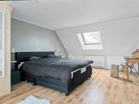 De ruime ouderlijke slaapkamer is voorzien van een sfeervolle vide en een directe toegang tot de badkamer.