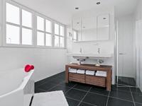 De moderne badkamer is volledig betegeld en voorzien van een dubbele wastafelcombinatie, toilet, douche en ligbad.
