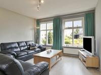 Lichte doorzon woonkamer met een laminaatvloer, spuitwerk wanden en plafond met aan de achterzijde de doorgang naar de keuken.