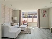 Royale woonkamer met deels gladde stucwerk wanden met behang en deels spachtelputz wanden, stucwerk plafond en toegang tot de trapkast waar de warmtepomp is opgesteld.