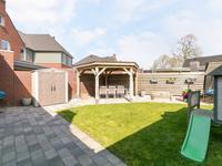 Leuk aangelegde achtertuin met gazon, bestrating en prachtige overkapping voor de mooie avond zon.