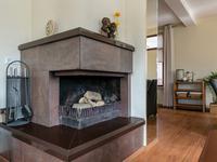 De schouw met open haard biedt een heerlijk plekje aan de voorzijde van de kamer. De schouw is gemaakt van natuursteen welke afkomstig is uit Afrika.