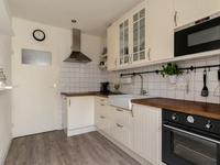 Semi-open keuken voorzien van diezelfde vloer en een mooie landelijke houten keukeninrichting welke is voorzien van een koelkast, keramische kookplaat, afzuigkap, magnetron, oven en vaatwasser. Tevens is er een grote inbouwkast aanwezig.