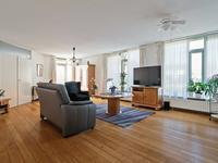 Vanuit de hal komt u in woonkamer welke u door zijn oppervlakte zal verrassen. Er is voldoende ruimte voor een mooie eethoek en een sfeervolle tv-/zithoek. De kamer heeft een houten vloer, spuitwerk wanden en plafond.
