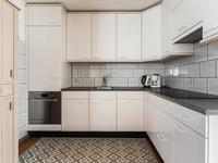 Er is een open keuken met een nette MDF inrichting en een kookplaat, afzuigkap, koelkast en vaatwasser.