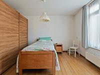 Aan de voorzijde van het huis zit een grote slaapkamer met een laminaat vloer en spuitwerk wanden en plafond.