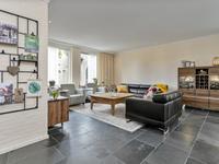 De woonkamer is breed van opzit met verschillende inrichtingsmogelijkheden met in het midden de gashaard. De wanden zijn deels gestuukt, deels geschilderde metselwerk wanden en het plafond is gestuukt en voorzien van diverse inbouwspots.