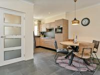 De deur naar de kamer is voorzien van glas. Aan de voorzijde is de keukenhoek opgesteld met een nette hoekkeuken voorzien van een granieten blad, koelkast, vaatwasser, gaskookplaat met wokpit, afzuigkap en combi magnetron. Direct bij de keuken is de eethoek met de twee treden verdiepte kelderkast.