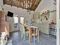 De ruimte is multifunctioneel en thans voorzienbare openslaande deuren naar de oprit, een bar, een keuken met een fornuis voorzien van oven. Bij de keuken / zitruimte is het plafond tot aan de nok toe open. <BR>Op de verdieping is een vide met aansluitend het nostalgische betegelde toilet met douche en wastafel. <BR>Dit luxe tuinhuis geeft de tuin en het buitenleven een extra dimensie.