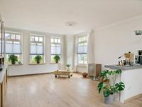 Doorzon woonkamer met een een warme houten vloer, lichte schuurwerk wanden en een strak stucwerk plafond. De kamer is zeer royaal en voorzien van veel lichtinval. Door de toegang naar de opkamer, de keuken en het werkblad in kamer is er ene speels indeling ontstaan. De opkamer is momenteel in gebruik als werk-/studeerkamer.