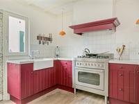 Semi-open landelijke keuken met een houten vloer, een houten balken plafond en stucwerk wanden. De keuken is in een U-opstelling geplaatst en voorzien van een 5 pits gasstel met oven, afzuigkap, koelkast en granieten aanrechtblad.