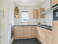 Aan de achterzijde is de woning in 2003 uitgebouwd en hierin is de keuken met een tegelvloer gesitueerd welke met een schuifdeur van de kamer gescheiden is. De keuken is netjes en biedt u een hoekinrichting met massieve deurtjes, een granieten aanrechtblad, een 5-pits gaskookplaat met wokbrander en daarboven een RVS afzuigkap, vaatwasmachine, koelkast en een combi-magnetron.