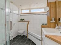 De badkamer is in 2003 volledig betegeld en ingericht met een hoekligbad, een douchecabine met thermostaatkraan, vaste wastafel met katsmeubel en spiegel, een 2e toilet en designradiator.