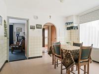 De woonkeuken is ruim van opzet en heeft een tegelvloer, tegellambrisering en een praktische inbouwkast.
